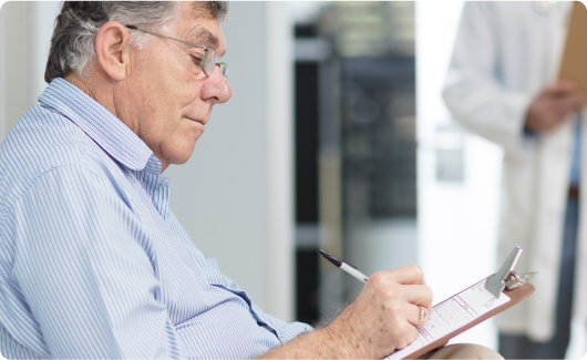 Man signing paperwork in medical office